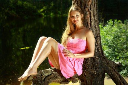 jeune fille assise sur une branche de pin, près du lac de la forêt