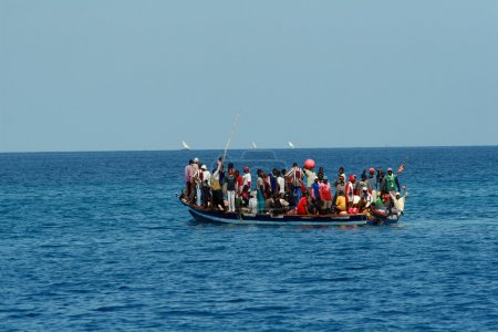 In ocean floats your boat with large group of Africans.