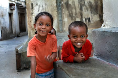 African, dark skinned children, about 5 years old, playing outdoors.