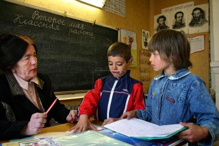 Clase de escuela en la escuela rusa de la aldea, un profesor de escuela se comunica con los estudiantes .