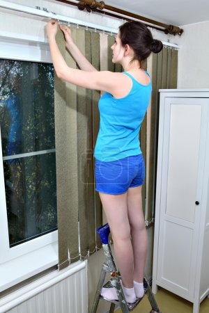 Girl installs dense fabric vertical blinds, click into place slats