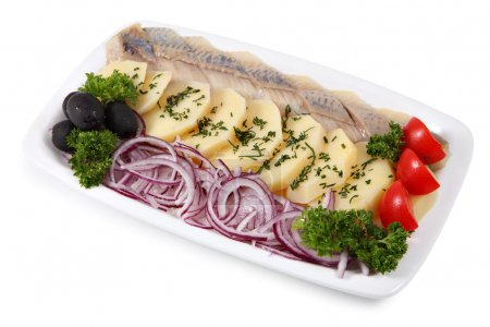 Plate with slices of pickled herring, onion, and boiled potatoes