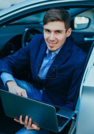 Smiling handsome businessman sitting in car
