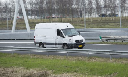 White Mercedes Sprinter driving down the road