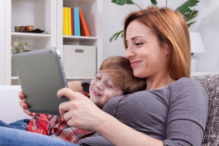 Photo pour Sourire, mère et fils à l'aide de tablette - image libre de droit