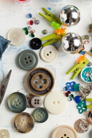 Photo pour Collection de divers boutons et petites broches sur table en bois blanc - image libre de droit
