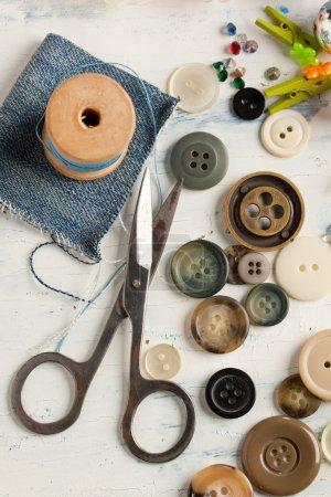 Photo pour Collection de divers boutons avec fil et ciseaux sur table en bois blanc - image libre de droit