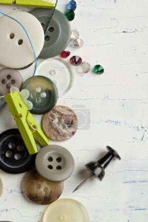 Photo pour Collection de divers boutons avec broches et cristaux sur table en bois blanc - image libre de droit