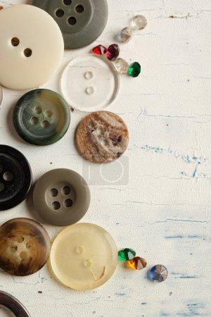 Photo pour Collection de divers boutons et cristaux sur table en bois blanc - image libre de droit