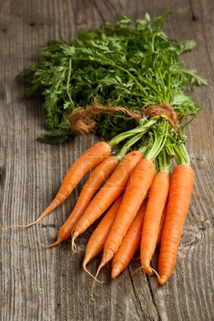 Photo for Freshly washed whole carrots on old wooden table - Royalty Free Image