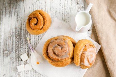 Photo pour Petits pains à la cannelle sucrés avec sucre et lait sur table en bois blanc - image libre de droit