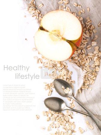 Photo pour Vue du dessus sur la moitié pomme avec des cultures flocons d'avoine et cuillères vintage sur textile sur blanc avec échantillon de texte - image libre de droit