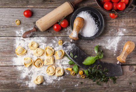 Photo for Top view on homemade pasta ravioli on old wooden table with flour, basil, tomatoes and vintage kitchen accessories - Royalty Free Image