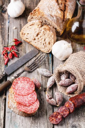 Sandwich and set of salami sausages with fresh bre...