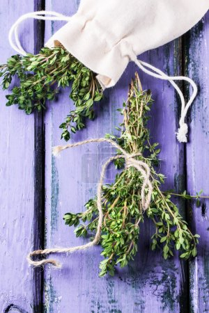 Thyme on violet wooden table