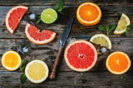 Photo for Set of sliced citrus fruits lemon, lime, orange, grapefruit with mint, ice and vintage knife over wooden background. Top view. - Royalty Free Image
