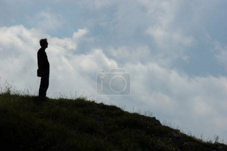Silhouette of a man standing on a hill