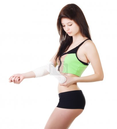 Young girl in a sports tank top and shorts is bandaging his arm with an elastic bandage