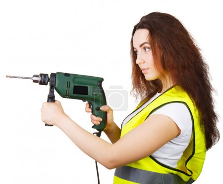 the girl in a construction vest with an electric drill in hands.