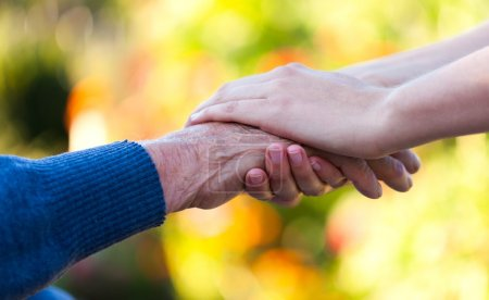 Photo for Young female hand holding an old man's hand. - Royalty Free Image