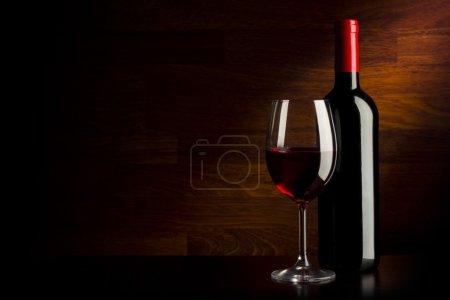 Photo pour Verre à vin et bouteille sur un fond en bois - image libre de droit