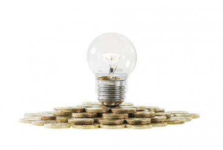 Photo pour Financement de la recherche et investissement dans l'innovation et le concept d'idées. Une ampoule claire avec un filament lumineux sur un tas de pièces . - image libre de droit