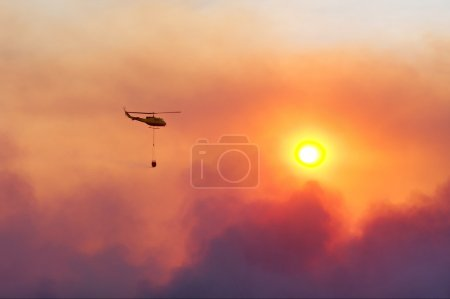 Fire rescue helicopter damping fire against sunset