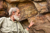 Old man points at the ancient bushman paintings
