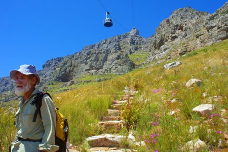 Old man walks down the trail under cable car