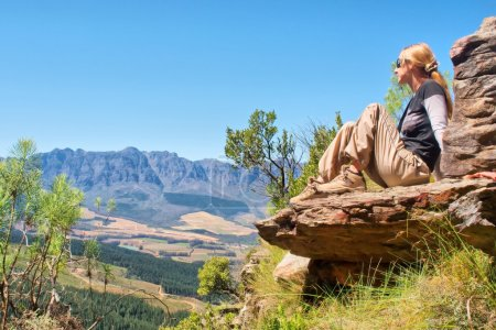 Blonde girl sits on rock and looks at mountains