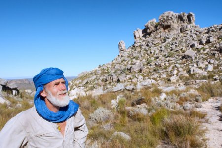 Old man in bedouin clothes looks at mountains