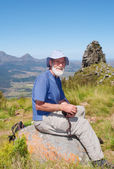 Senior hiker rests on rock