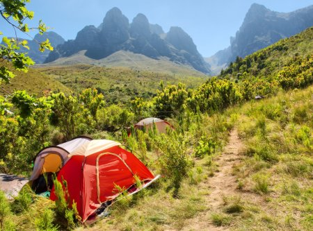 Red camping tent next to trail in mountains