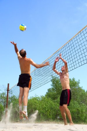 Two men playing beach volleyball - short balding man wins over t