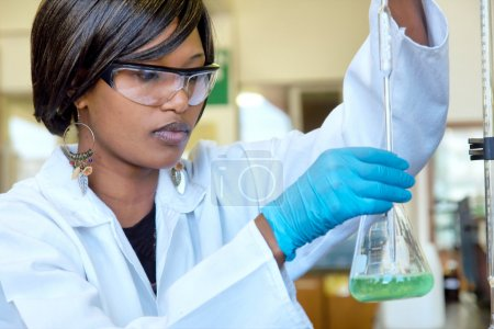 African female researcher works with a glass in the lab