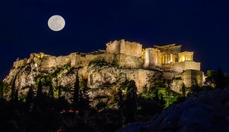 Photo for Acropolis by moonlight. Night. The full moon and the light of lanterns light up the Acropolis. The trees in the background and lighting. In the foreground is the ancient stones in the moonlight. - Royalty Free Image