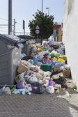 Bags full of trash surrounding dumpsters, vertical