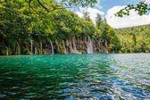 Beautiful clear blue lake and small waterfall in Plitvice
