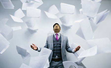 Photo pour Homme d'affaires occupé avec une pile de papiers volants sur les airs - image libre de droit