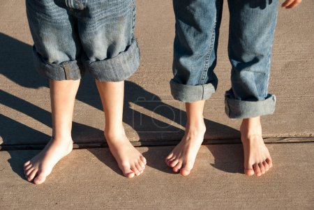 Children with bare feet and pants rolled up