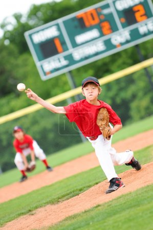 Young baseball player pitching the ball