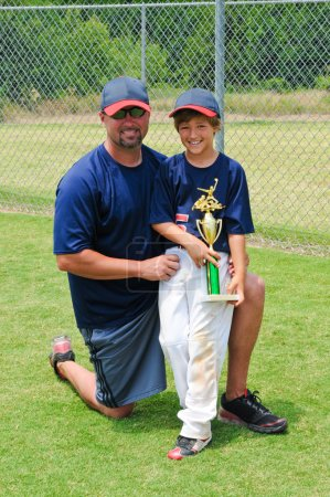 Father and son baseball player with trophy.
