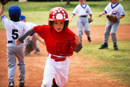 Photo pour Petit joueur de baseball de Ligue exécute les bases dans un jeu - image libre de droit