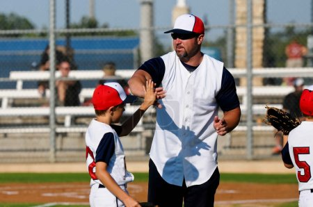 Little league baseball player with coach