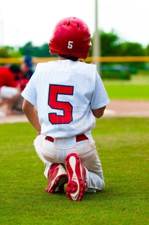 Kneeling baseball boy for injured player