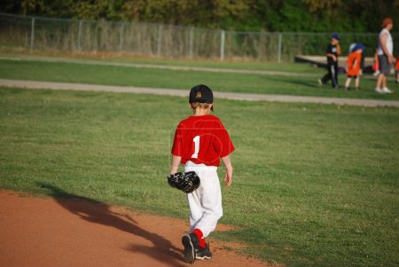 Young baseball player walking on field
