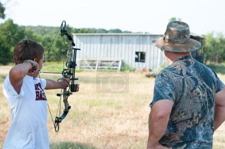 teen boy with grandpa shooting bow
