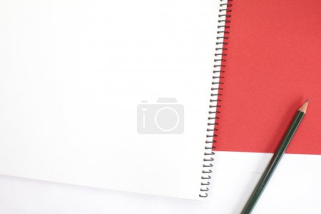 Opened white notebook with pencil