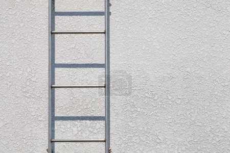 Metal ladder against gray wall