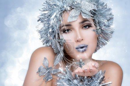 Photo pour Femme à la mode avec des lèvres sensuelles et un stylisme fantastique. Vogue modèle de style souffler sa main - image libre de droit